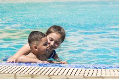 Smiling boy and little girl swimming in pool in aquapark. Summer vacation concept. Space for text royalty free stock photos