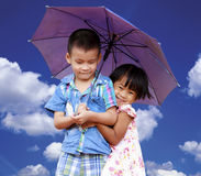 Smiling boy and little girl with umbrella Stock Photos