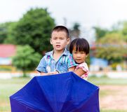 A smiling boy and a little girl with umbrella Stock Photo