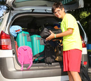 Smiling boy loads bags in the baggage car Royalty Free Stock Photography