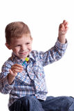 Smiling boy with a lollipop in his hand. On a light background Stock Photo