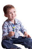 Smiling boy with a lollipop in his hand. On a light background Royalty Free Stock Photography