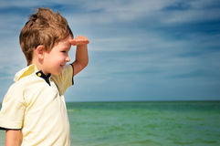 Smiling boy looking away from his palm on the background of clou. Dy sky and sea. horizontal Stock Image