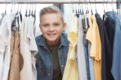 Smiling boy looking at camera surrounded by clothes on hanger. At store Royalty Free Stock Photos