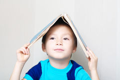 Smiling boy looking forward making book roof Stock Image