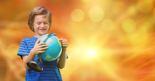 Smiling boy looking at globe over bokeh Royalty Free Stock Photo