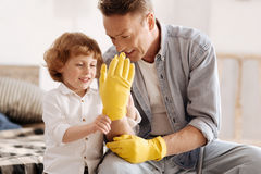 Smiling boy looking at hand of his dad Stock Images