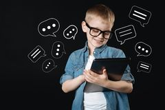 Smiling boy looking at the screen while holding a big new tablet. Typing messages. Cheerful cute smiling child kindly looking at the screen of a big modern royalty free stock photo