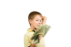 Smiling boy looking at a stack of 100 US dollars b. Ills and think what to do. isolated on white background Royalty Free Stock Image