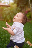 Smiling boy looking up. Sitting on park green grass Stock Images