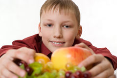 Smiling boy looks at the fruit Stock Photography