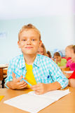 Smiling boy looks while writing in exercise book Stock Photos