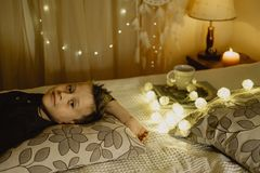 Smiling boy lying in bed evening in dark against the background. Of lanterns Stock Photo