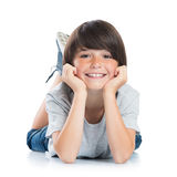 Smiling boy lying on floor. Closeup of smiling little boy with freckles lying on white background. Happy cute male child lying on white floor and looking at Royalty Free Stock Images