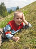 Smiling boy lying on grass Royalty Free Stock Image