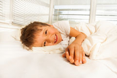 Smiling boy lying in his bed looking at camera Stock Photography