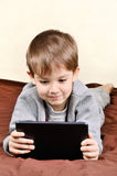 Smiling boy is lying and playing on a tablet. On a light and brown background vertical. Boy 5 years Stock Photography