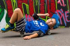 Smiling Boy Lying on Skateboard in Urban Park Royalty Free Stock Image