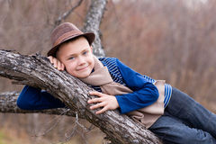 Smiling boy lying on a tree. Stock Photos