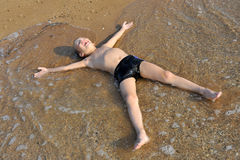 Smiling boy lying in water at the beach Stock Image