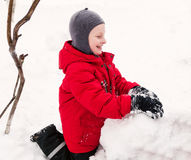Smiling boy making snowman. Stock Image