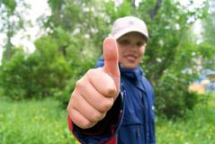Smiling boy making thumb up. Outdoor Royalty Free Stock Image