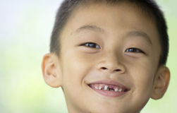 Smiling boy with missing teeth. A Chinese boy smiling with front teeth missing Royalty Free Stock Photo