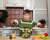 Smiling boy mixing a vegetable salad in the kitchen. Stock Photos