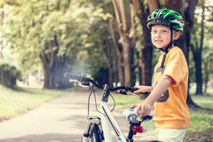 Smiling boy with new bicycle in park Stock Photo