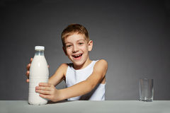 Smiling boy opening bottle of milk Stock Photography