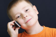 Smiling boy in orange with cellphone Stock Photo