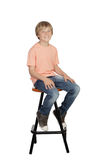 Smiling boy with orange t-shirt sitting on a stool Royalty Free Stock Image