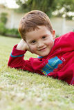 Smiling boy outsise on lawn Stock Photos
