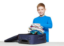 Smiling boy packing luggage bag with clothes Royalty Free Stock Photography