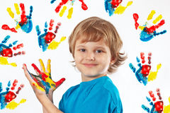 Smiling boy with painted hands on background of hand prints royalty free stock photo