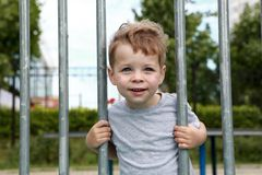Smiling boy on fence background. Smiling boy in park on fence background stock photography