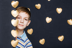 Smiling boy peeking on golden hearts background Royalty Free Stock Images
