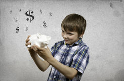 Smiling boy with a piggybank Stock Images