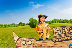 Smiling boy in pirate costume holds the helm Stock Images
