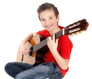 Smiling boy is playing on acoustic guitar Royalty Free Stock Images