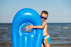 Smiling boy playing on the beach with air mattress Stock Photo