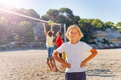 Smiling boy playing beach volleyball with friends. Portrait of smiling teenage boy playing beach volleyball with friends stock photos