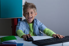 Smiling boy playing computer Royalty Free Stock Image