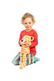 Smiling boy playing with fluffy tiger. Isolated on white background Stock Image