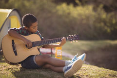 Smiling boy playing guitar in park Stock Photo