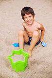 Smiling boy playing in sand Royalty Free Stock Image
