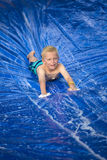Smiling boy playing on a slip and slide outdoors Royalty Free Stock Photos