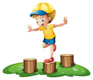 A smiling boy playing with the stumps Royalty Free Stock Photography