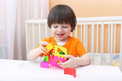 Smiling boy plays educational toy Stock Images