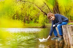 Smiling boy plays with white paper boat near pond Stock Photos